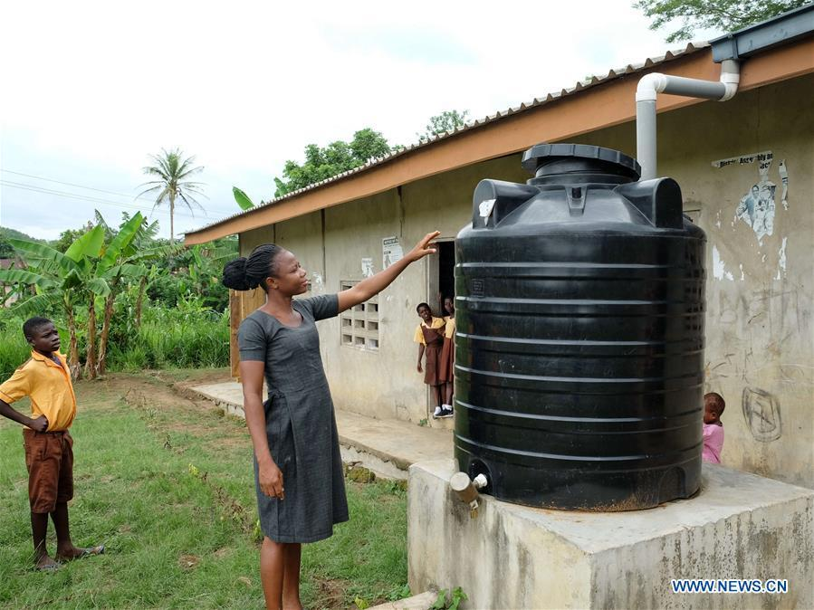 A primary school teacher shows a water tank which used to gather the rainwater from rooftops in Guayotse Village, Eastern Region, Ghana, on June 18, 2018. The government of China is providing 1,000 boreholes for hundreds of rural communities in six out of the ten regions of Ghana to bring clean water to the people. (Xinhua/Zhao Shuting)