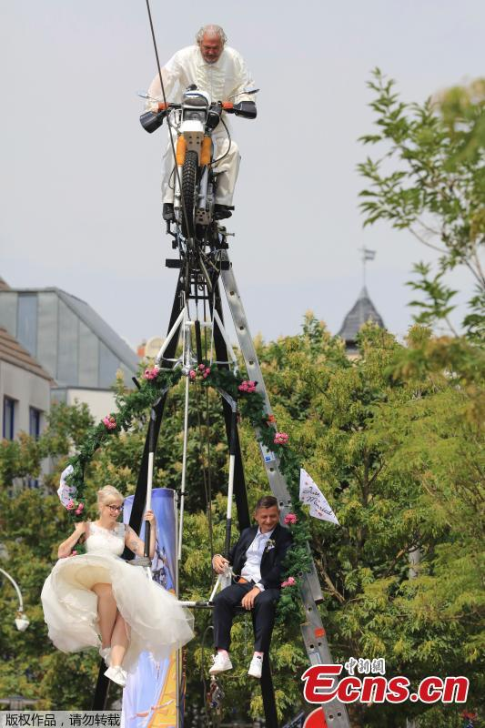 The high-wire artist Falko Traber drives the bridal couple Nicole Backhaus and Jens Knorr during the wedding ceremony atop a tightrope in Stassfurt, Germany, June 16, 2018. (Photo/Agencies)