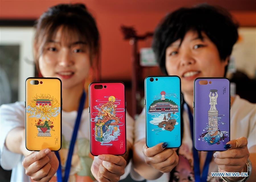 Staff members show smartphone cases with creative designs based on China\'s traditional 24 solar terms at a souvenir shop in Beihai Park, Beijing, capital of China, June 20, 2018. The 24 solar terms are a list of terms central to a calendar created in ancient China. Based on the movement of the sun, the calendar divides the year into 24 segments to guide farming over the four seasons. (Xinhua/Xing Guangli)