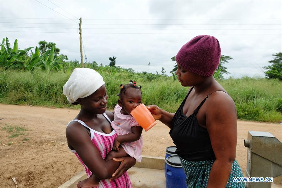 A woman gives water to a baby near a borehole in Agyakwa Village, Eastern Region, Ghana, on June 18, 2018. The government of China is providing 1,000 boreholes for hundreds of rural communities in six out of the ten regions of Ghana to bring clean water to the people. (Xinhua/Zhao Shuting)