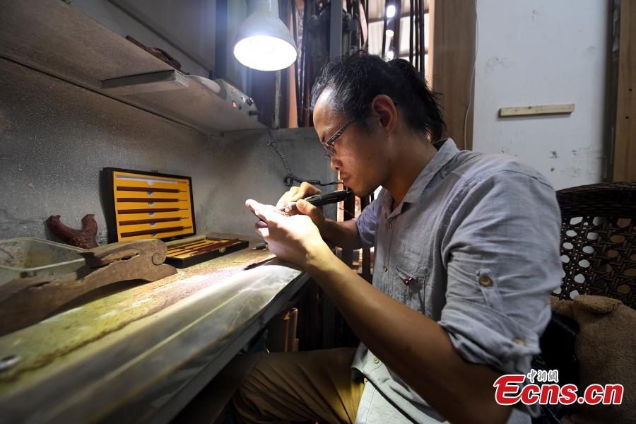 Jade carving craftsman Qian Siyu works in his studio in Nanning City, South China's Guangxi Zhuang Autonomous Region, June 20, 2018. Qian, born in 1984, is known for combining the elements of the culture and traditions of the Zhuang ethnic group into his designs. (Photo: China News Service/Yu Jing)