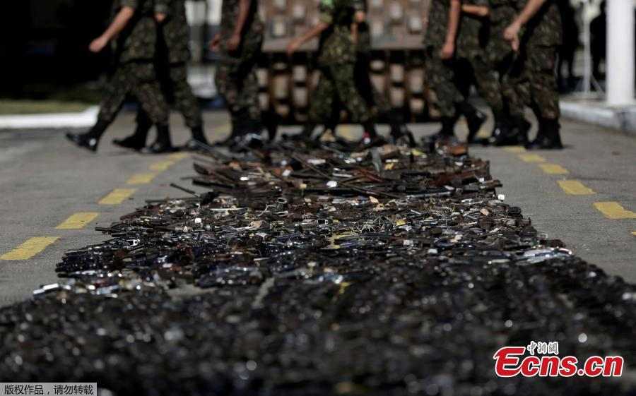Brazilian Army soldiers walk past by guns seized from criminals by armed forces before being destroyed in Rio de Janeiro, Brazil, June 20, 2018. The Brazilian army invited the media Wednesday to observe the destruction of 8,549 firearms seized from criminals, handed in voluntarily, or retired from police arsenals. (Photo/Agencies)