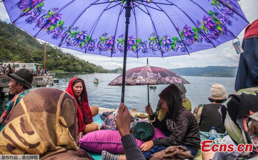 Family members sit together as they wait for rescue teams searching for missing passengers at the Lake Toba ferry port in the province of North Sumatra on June 20, 2018, after a boat capsized on June 18. The death toll from an Indonesian ferry disaster could top 180, as authorities raised an estimate of the number of people missing two days after the wooden tourist boat sank in Lake Toba on the island of Sumatra. (Photo/Agencies)