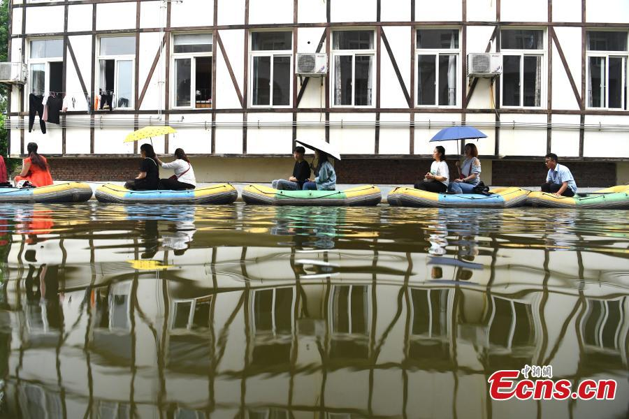 Tourists take boats on an artificial canal during their visit to a wine town in Fuling District, Southwest China's Chongqing Municipality, June 20, 2018. The five-kilometer-long canal includes a section that passes through a building. (Photo: China News Service/Chen Chao)