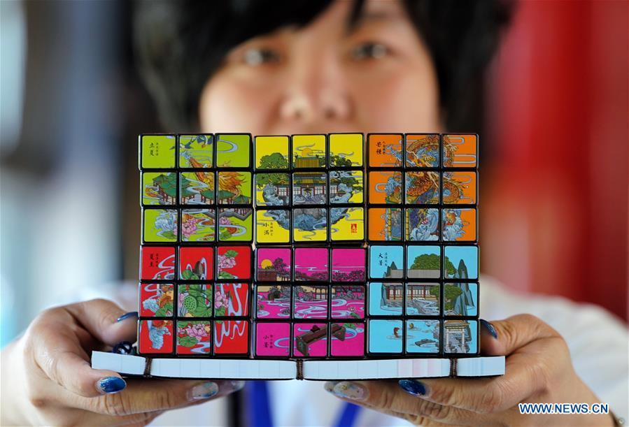 A staff member shows Rubik\'s Cubes with creative designs based on China\'s traditional 24 solar terms at a souvenir shop in Beihai Park, Beijing, capital of China, June 20, 2018. The 24 solar terms are a list of terms central to a calendar created in ancient China. Based on the movement of the sun, the calendar divides the year into 24 segments to guide farming over the four seasons. (Xinhua/Xing Guangli)