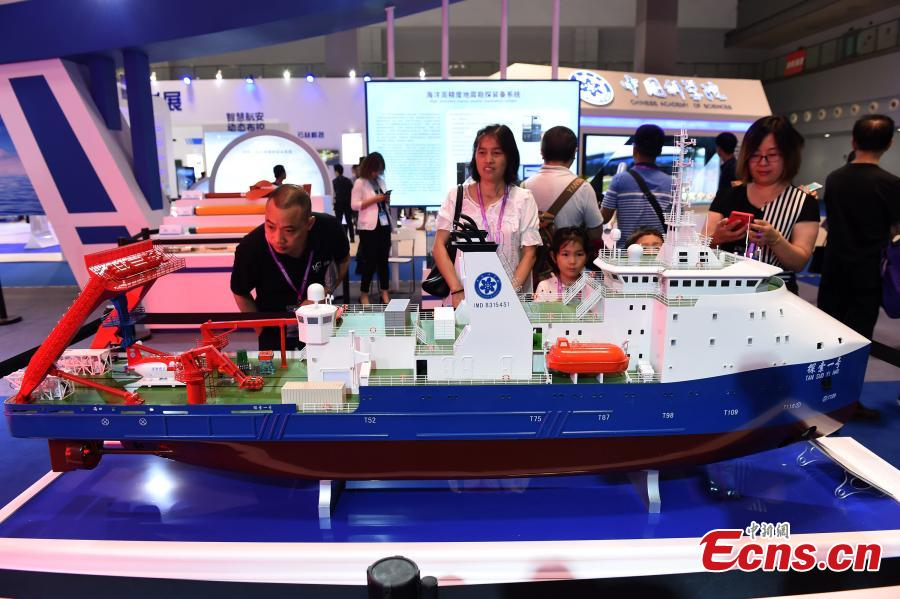 Visitors look at a model of the oceanic research vessel Tansuo-1, mother ship for manned submersible Shenhai Yongshi, at the 9th International Military and Civilian Dual-use Technology Exhibition in Chongqing, June 21, 2018. (Photo: China News Service/Zhou Yi)