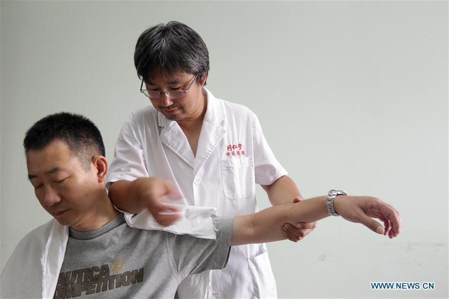 File photo taken on July 29, 2010 shows a doctor providing tui na treatment for a patient at a hospital of the Tongrentang, a renowned traditional Chinese medicine maker, in Beijing, capital of China. Traditional Chinese medicine (TCM), one of the world\'s oldest forms of medicine with different practices including acupuncture, bee-sting therapy, cupping, moxibustion, scrapping, tui na (Chinese therapeutic massage), still prevails in the modern society after thousands of years of evolution, during which generations have restored and maintained health depending on it. The World Health Organization disease index was updated to include references to traditional Chinese medicine for the first time in June 2018. (Xinhua/Xing Guangli)