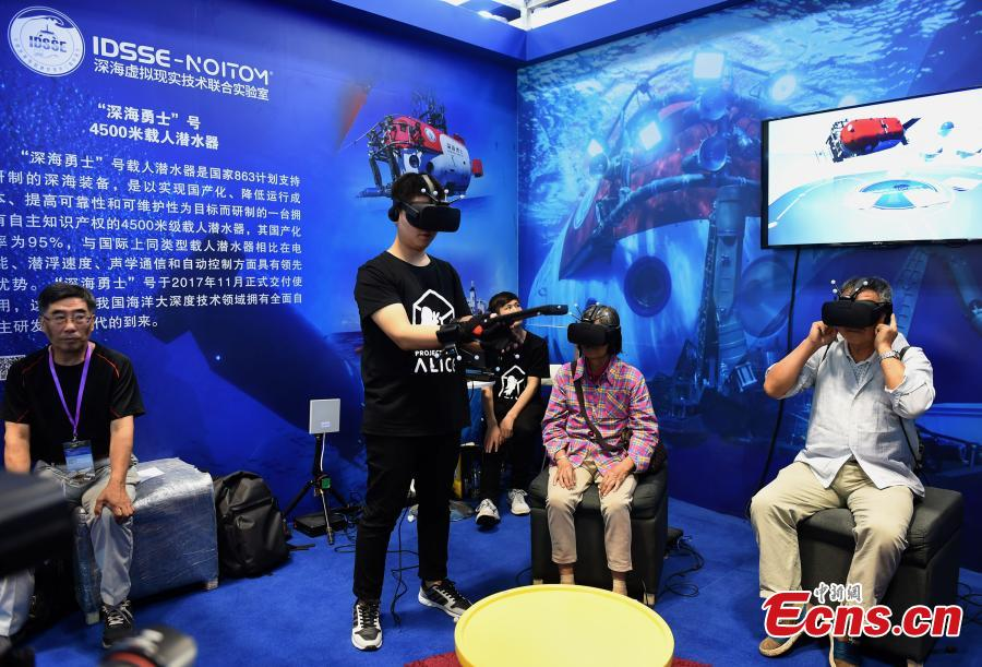 Visitors use VR to try out the manned submersible Shenhai Yongshi at the 9th International Military and Civilian Dual-use Technology Exhibition in Chongqing, June 21, 2018. (Photo: China News Service/Zhou Yi)