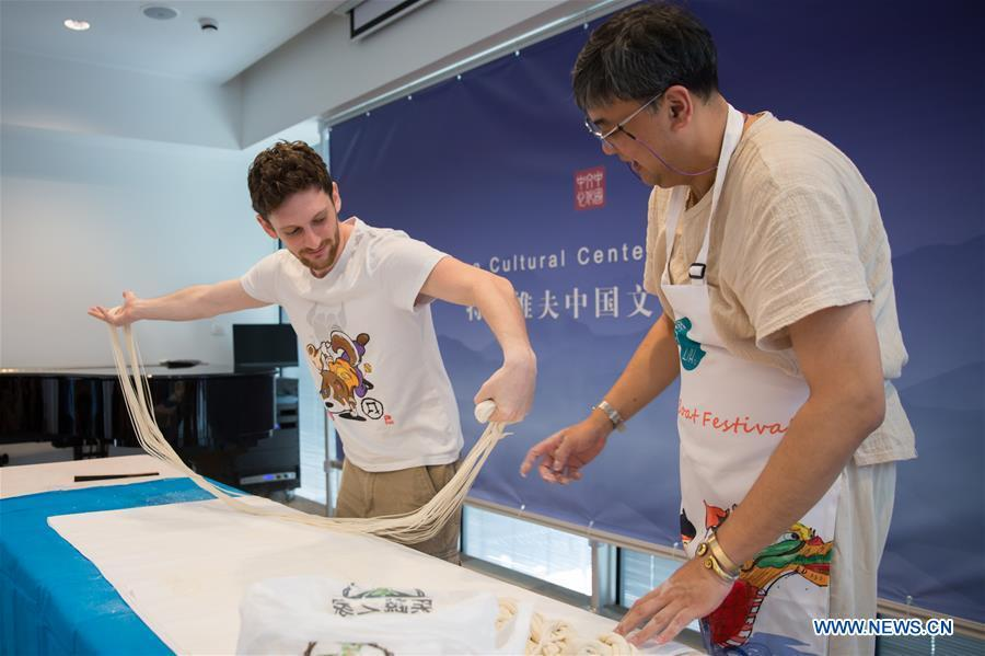 An Israeli man (L) learns noodle making skills during a Chinese food festival event at the Chinese Cultural Center in Tel Aviv, Israel, on June 22, 2018. (Xinhua/Guo Yu)