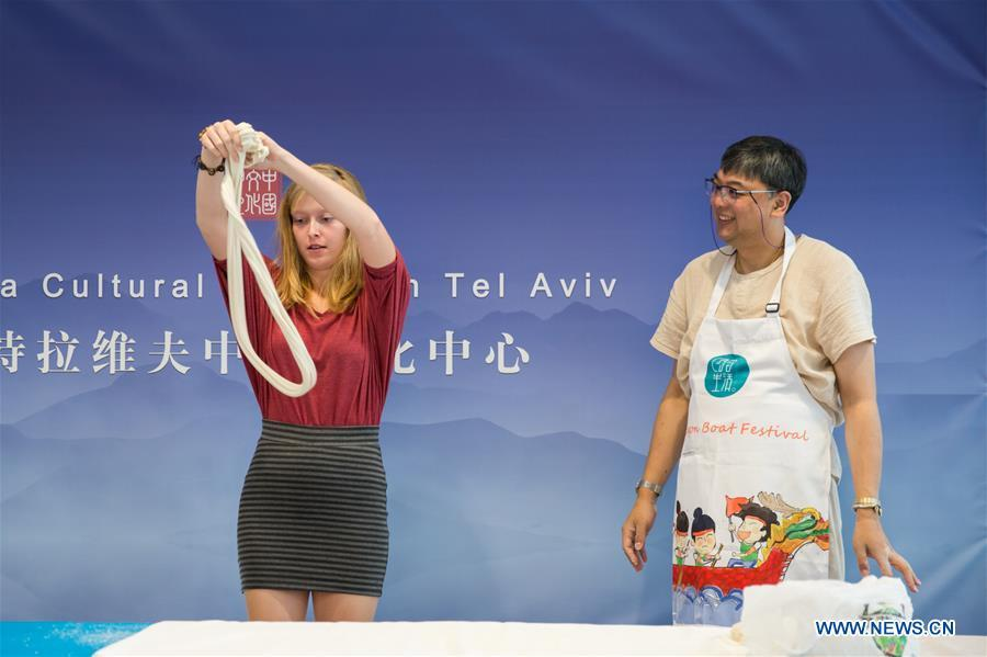 An Israeli girl (C) learns noodle making skills during a Chinese food festival event at the Chinese Cultural Center in Tel Aviv, Israel, on June 22, 2018. (Xinhua/Guo Yu)