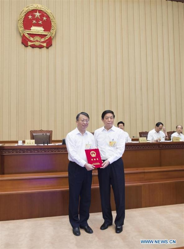 Li Zhanshu (R, front), chairman of the National People\'s Congress (NPC) Standing Committee, grants certificate of appointment to a member of the Hong Kong basic law committee of the NPC Standing Committee during a bimonthly session of the 13th NPC Standing Committee at the Great Hall of the People in Beijing, capital of China, June 22, 2018. The bimonthly session concluded here on Friday. (Xinhua/Li Tao)
