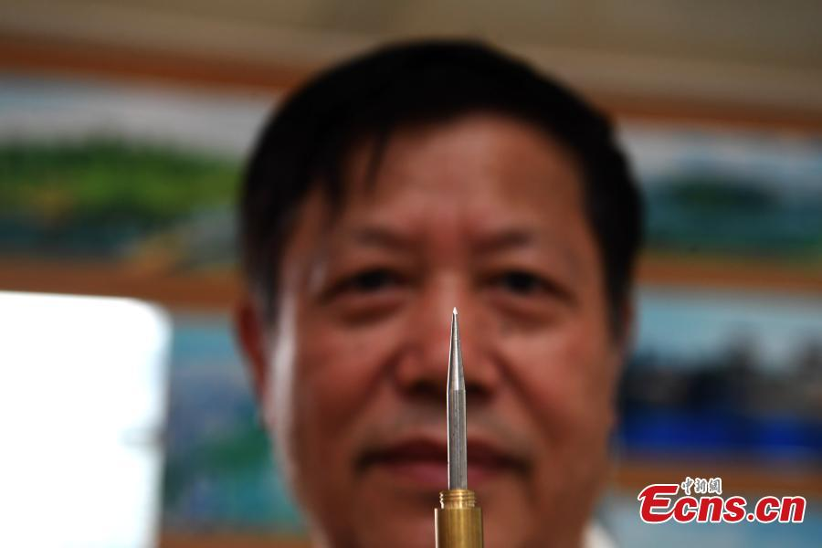 Pan Qihui shows a tool he uses to make miniature carvings at an exhibition in Chongqing, June 23, 2018. The smallest characters carved by Pan are as thin as a hair and a magnifying glass is needed to see them. (Photo: China News Service/Chen Chao)