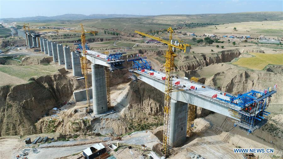 In this aerial photo taken on June 23, 2018, workers construct a bridge in the Gansu-Ningxia section of the Yinchuan-Xi\'an high-speed railway in northwest China\'s Ningxia Hui Autonomous Region. The 617-kilometer high-speed railway is scheduled to start operation by the end of 2020 with a design speed of 250 kilometers per hour. (Xinhua/Wang Peng)