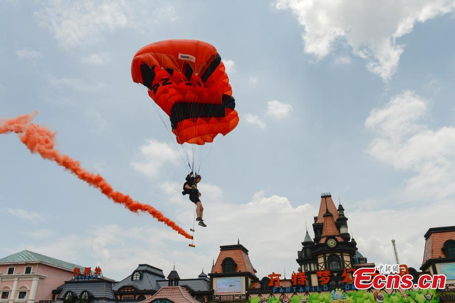 Shi Chunyan, a female BASE jumper, successfully jumps from a helicopter at a height of 300 meters at a theme park in Zhuzhou City, Central China's Hunan Province, June 23, 2018. When the helicopter reached the planned height, she jumped off and landed safely using a parachute in the 60-second challenge. (Photo: China News Service/Yang Huafeng)