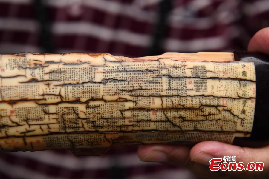 Pan Qihui shows miniature calligraphy he carved at an exhibition in Chongqing, June 23, 2018. The smallest characters carved by Pan are as thin as a hair and a magnifying glass is needed to see them. (Photo: China News Service/Chen Chao)