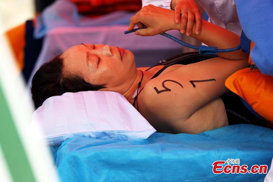 An exhausted participant breathes oxygen after finishing a swimming race across the Yellow River in Xunhua Salar Autonomous County, Northwest China's Qinghai Province, June 24, 2018. The race on China's second longest river was 500 meters long. (Photo: China News Service/Zhang Tianfu)
