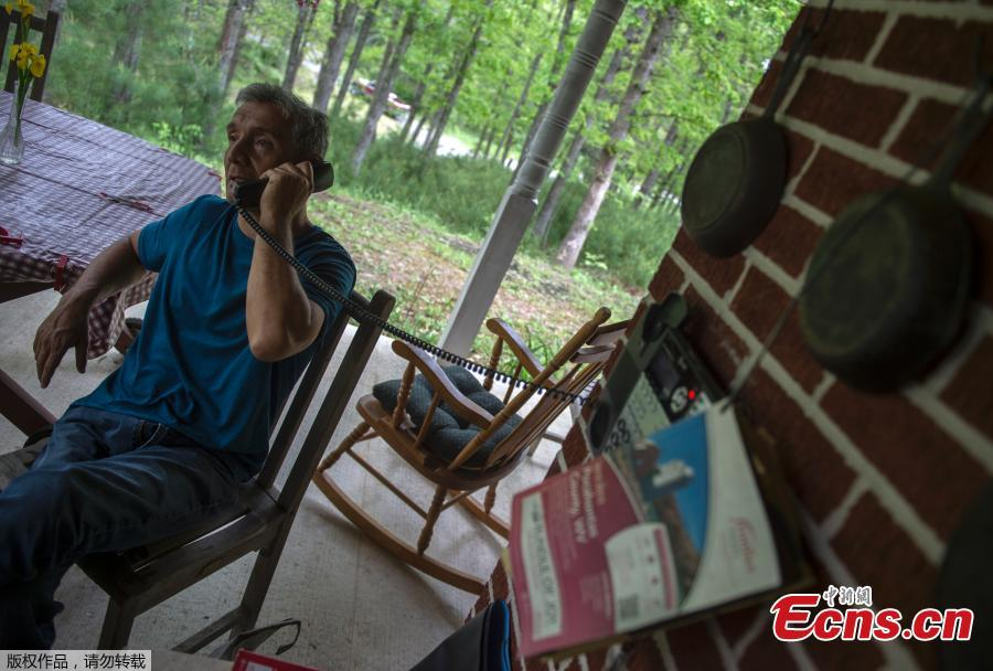 Carlos Sosa speaks on a wired phone in Green Bank, West Virginia on May 28, 2018.  Carlos Sosa believes he suffers from Electromagnetic Hypersensitivity (EHS), which they say is caused by exposure to electromagnetic fields typically created by mobile phones, wi-fi and other electronic equipment. He lives in Green Bank which is part of the US Radio Quiet Zone, where wireless telecommunications signals are banned to prevent transmissions interfering with a number of radio telescopes in the area. The largest steerable telescope in the world, the Green Bank Telescope, enables scientists to listen to low-level signals from different places in the universe. (Photo/Agencies)