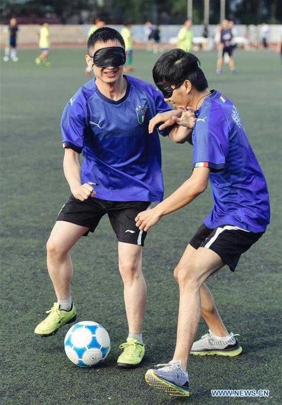 Sun Dongyuan (R) and Fan Changjie play football at the special education school of Changchun University in northeast China\'s Jilin Province, June 20, 2018. Sun Dongyuan and Fan Changjie, who were diagnosed with congenital eye disease, learn acupuncture and massage in the school. They are also players of the school\'s football team for visually impaired students. During the match, Sun and Fan identify position via a bell inside the ball and with guides\' instructions. The FIFA World Cup 2018 has become their popular topic since June 14, and they listen to the live broadcast and cheer for their favorite teams. (Xinhua/Xu Chang)