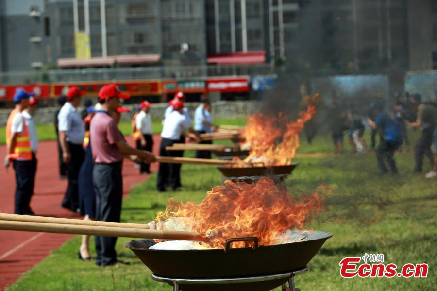 Police burn 40 kilograms of seized drugs in an event to mark the International Day Against Drug Abuse and Illicit Trafficking in Liuzhou City, South China's Guangxi Zhuang Autonomous Region, June 26, 2018. Over 4,000 people participated the event. (Photo: China News Service/Zhu Liurong)