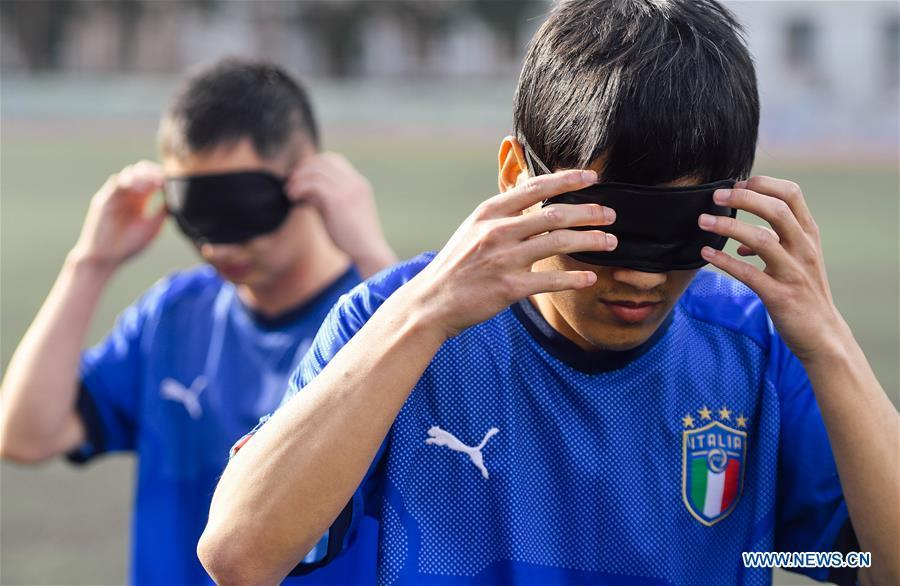 Sun Dongyuan (front) and Fan Changjie wear eyeshades before a training at the special education school of Changchun University in northeast China\'s Jilin Province, June 20, 2018. Sun Dongyuan and Fan Changjie, who were diagnosed with congenital eye disease, learn acupuncture and massage in the school. They are also players of the school\'s football team for visually impaired students. During the match, Sun and Fan identify position via a bell inside the ball and with guides\' instructions. The FIFA World Cup 2018 has become their popular topic since June 14, and they listen to the live broadcast and cheer for their favorite teams. (Xinhua/Xu Chang)
