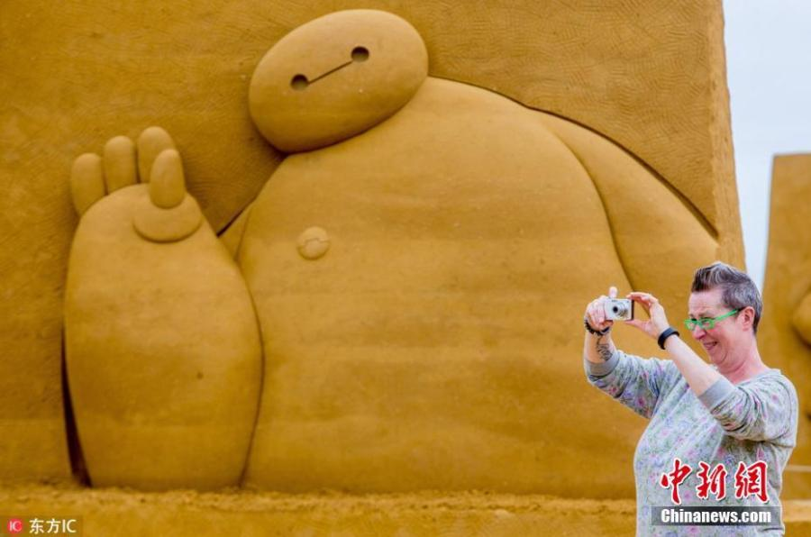 A visitor takes photos beside a sculpture during the Sand Sculpture Festival \