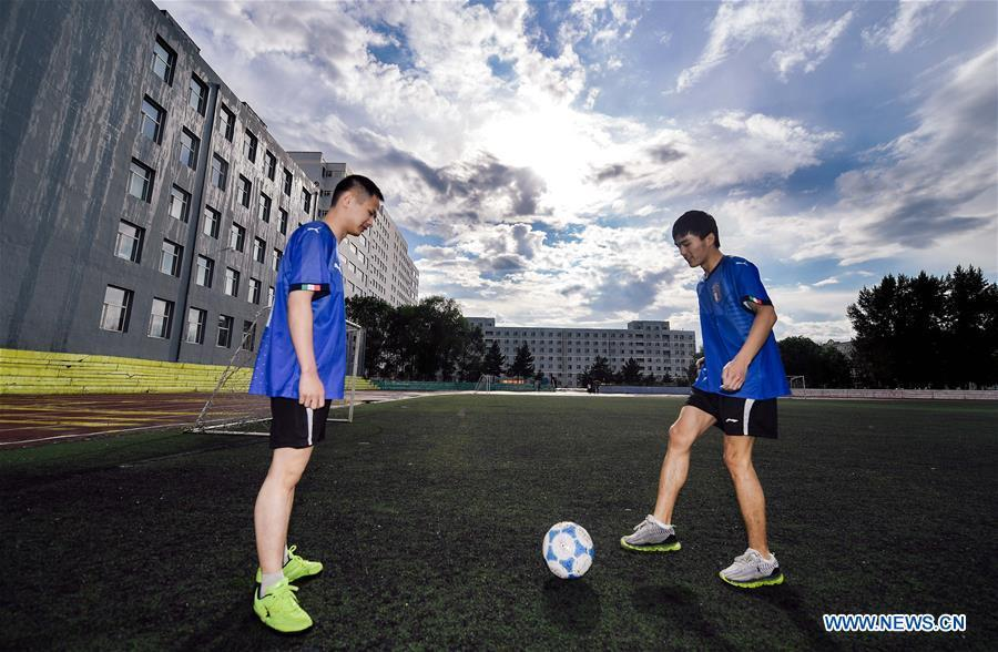 Sun Dongyuan (R) and Fan Changjie have a football training at the special education school of Changchun University in northeast China\'s Jilin Province, June 20, 2018. Sun Dongyuan and Fan Changjie, who were diagnosed with congenital eye disease, learn acupuncture and massage in the school. They are also players of the school\'s football team for visually impaired students. During the match, Sun and Fan identify position via a bell inside the ball and with guides\' instructions. The FIFA World Cup 2018 has become their popular topic since June 14, and they listen to the live broadcast and cheer for their favorite teams. (Xinhua/Xu Chang)