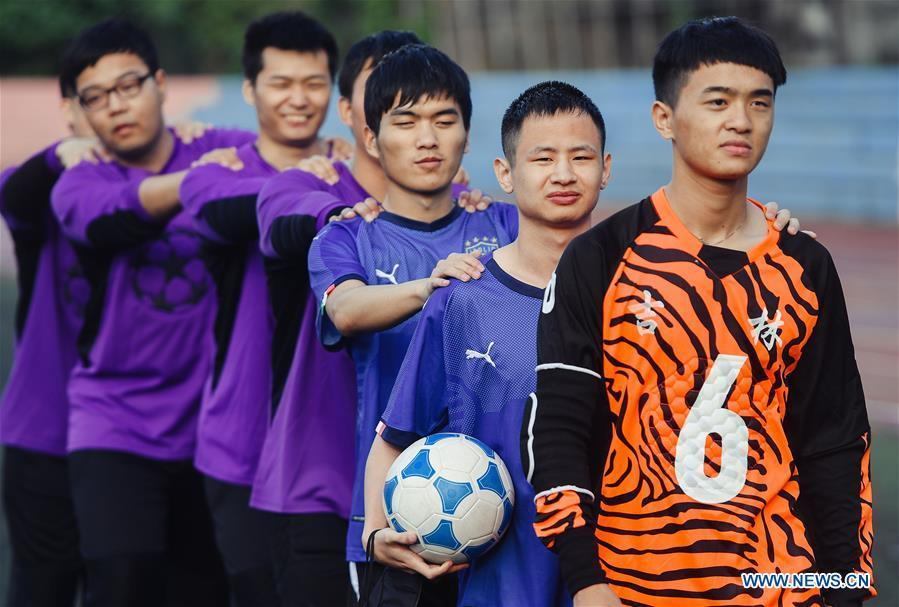 Football players of the special education school of Changchun University walk to the playground in Changchun, northeast China\'s Jilin Province, June 20, 2018. Sun Dongyuan and Fan Changjie, who were diagnosed with congenital eye disease, learn acupuncture and massage in the school. They are also players of the school\'s football team for visually impaired students. During the match, Sun and Fan identify position via a bell inside the ball and with guides\' instructions. The FIFA World Cup 2018 has become their popular topic since June 14, and they listen to the live broadcast and cheer for their favorite teams. (Xinhua/Xu Chang)