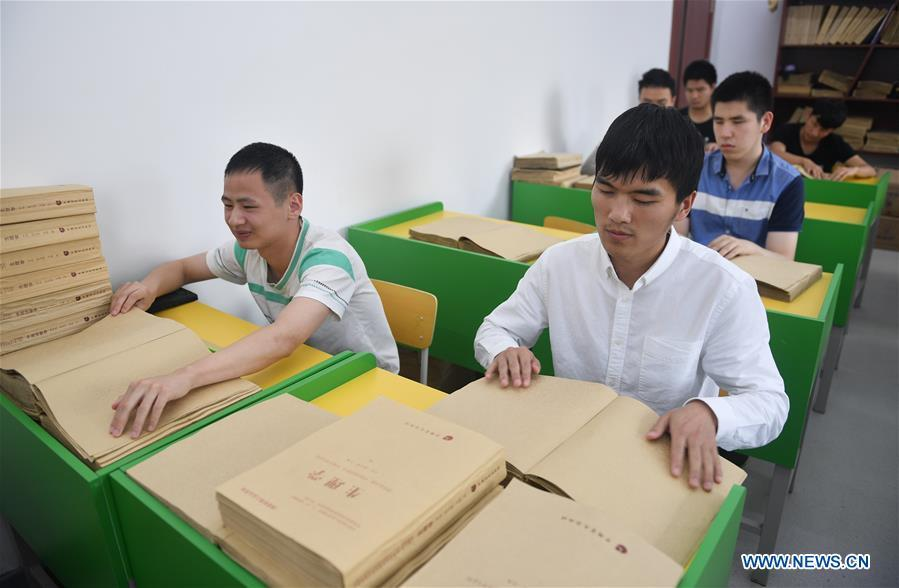 Sun Dongyuan (R, front) and Fan Changjie (L, front) read books for visually impaired students at the special education school of Changchun University in northeast China\'s Jilin Province, June 20, 2018. Sun Dongyuan and Fan Changjie, who were diagnosed with congenital eye disease, learn acupuncture and massage in the school. They are also players of the school\'s football team for visually impaired students. During the match, Sun and Fan identify position via a bell inside the ball and with guides\' instructions. The FIFA World Cup 2018 has become their popular topic since June 14, and they listen to the live broadcast and cheer for their favorite teams. (Xinhua/Xu Chang)