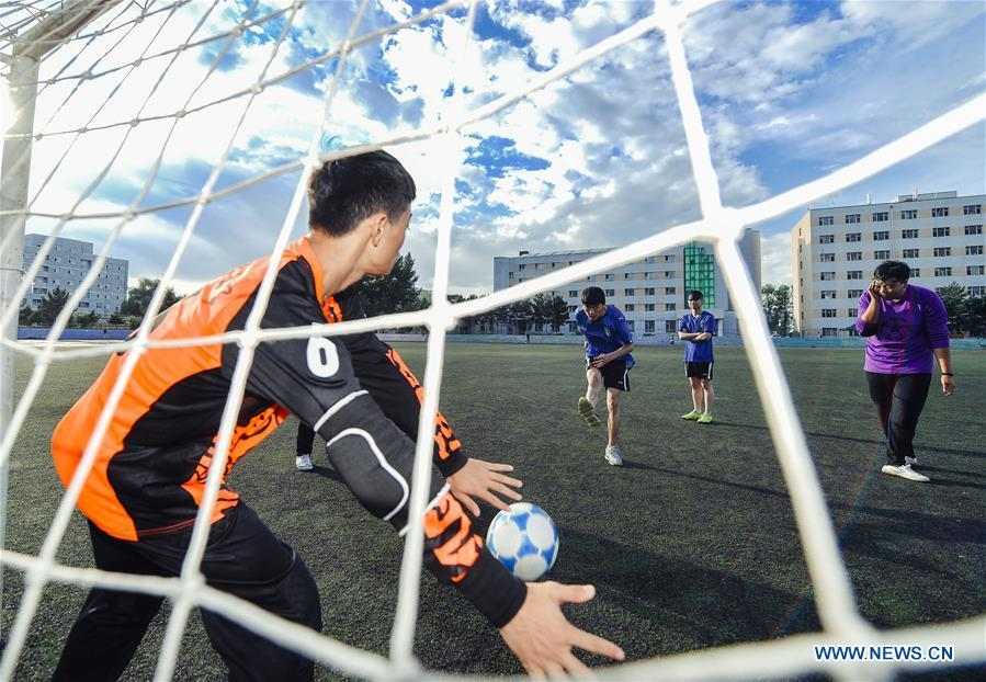 Sun Dongyuan (2nd L) and his teammates have a training at the special education school of Changchun University in northeast China\'s Jilin Province, June 20, 2018. Sun Dongyuan and Fan Changjie, who were diagnosed with congenital eye disease, learn acupuncture and massage in the school. They are also players of the school\'s football team for visually impaired students. During the match, Sun and Fan identify position via a bell inside the ball and with guides\' instructions. The FIFA World Cup 2018 has become their popular topic since June 14, and they listen to the live broadcast and cheer for their favorite teams. (Xinhua/Xu Chang)