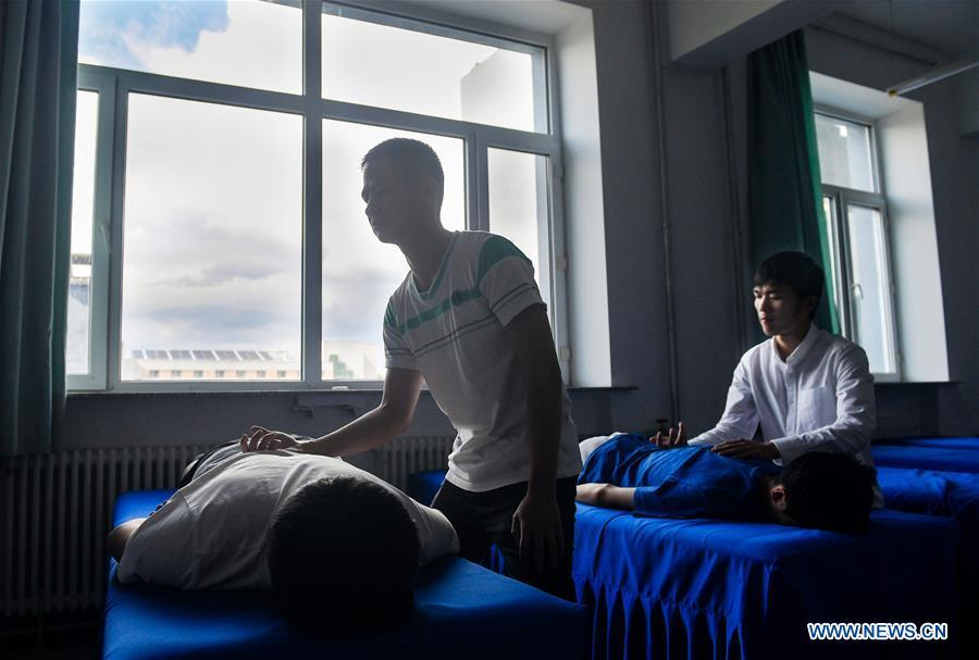 Sun Dongyuan (R) and Fan Changjie learn massage in a classroom at the special education school of Changchun University in northeast China\'s Jilin Province, June 20, 2018. Sun Dongyuan and Fan Changjie, who were diagnosed with congenital eye disease, learn acupuncture and massage in the school. They are also players of the school\'s football team for visually impaired students. During the match, Sun and Fan identify position via a bell inside the ball and with guides\' instructions. The FIFA World Cup 2018 has become their popular topic since June 14, and they listen to the live broadcast and cheer for their favorite teams. (Xinhua/Xu Chang)