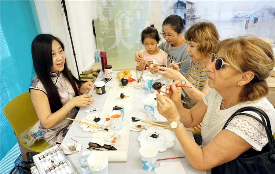Chinese folk artist Guan Hui (L) teaches visitors how to make gourd paintings in Tel Aviv, Israel, June 25, 2018.(Photo/Asianewsphoto)
