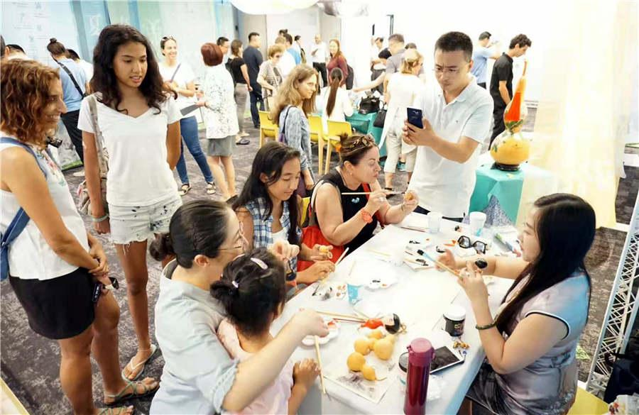Chinese folk artist Guan Hui teaches visitors how to make gourd paintings in Tel Aviv, Israel, June 25, 2018.(Photo/Asianewsphoto)