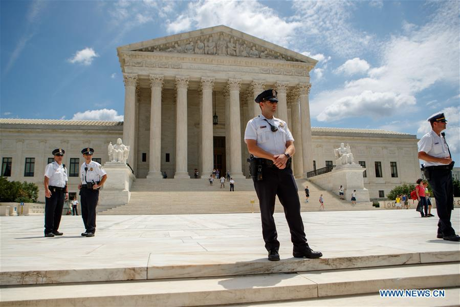 Police officers stand guard amid protest outside U.S. Supreme Court in Washington D.C., the United States, on June 26, 2018. U.S. Supreme Court on Tuesday ruled President Donald Trump\'s travel ban on several Muslim-majority countries is lawful. (Xinhua/Ting Shen)