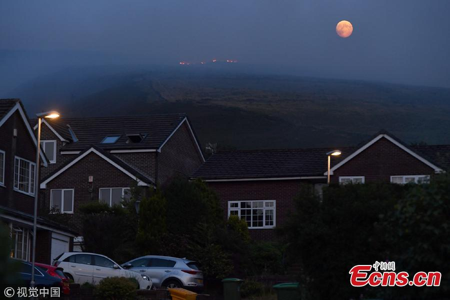 The full moon rises behind burning moorland as a large wildfire sweeps across the moors between Dovestones and Buckton Vale in Stalybridge, Greater Manchester in Stalybridge, England, June 26, 2018.  (Photo/VCG)