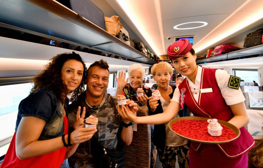 A steward hands out birthday cakes to passengers on the G1 Fuxing high-speed bullet train on Beijing-Shanghai high speed railway line on June 26, 2018. (Photo/Xinhua)