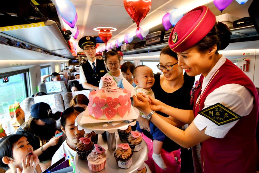 A steward holds a baby passenger\'s hands to cut the birthday cake on the G1 Fuxing high-speed bullet train on Beijing-Shanghai high speed railway line on June 26, 2018. (Photo/Xinhua)
