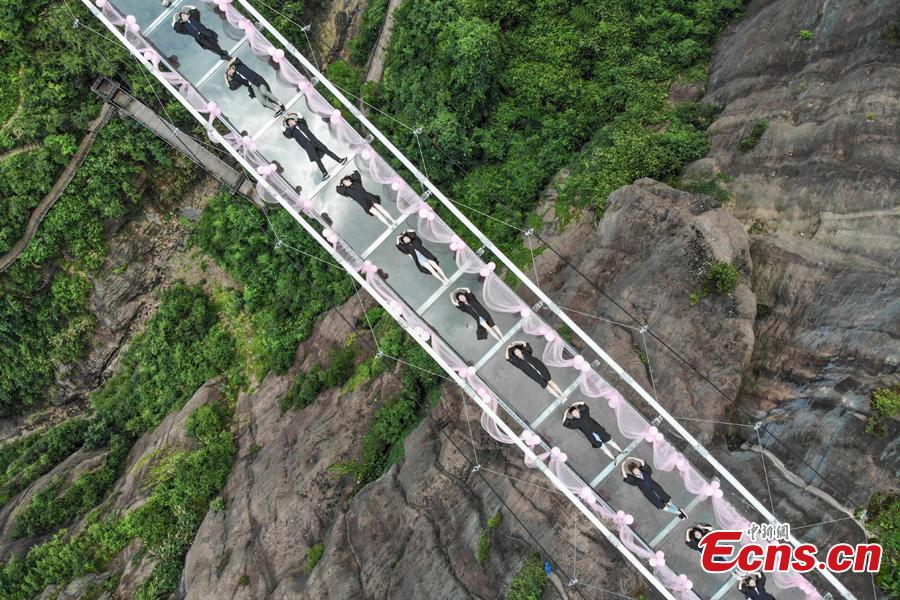 Students take creative graduation photos on a glass-bottom bridge in the Shiniuzhai National Geological Park in Pingjiang County, Central China\'s Hunan Province, June 27, 2018. The transparent bridge is suspended between two cliffs, 180 meters above ground. (Photo: China News Service/Yang Huafeng)