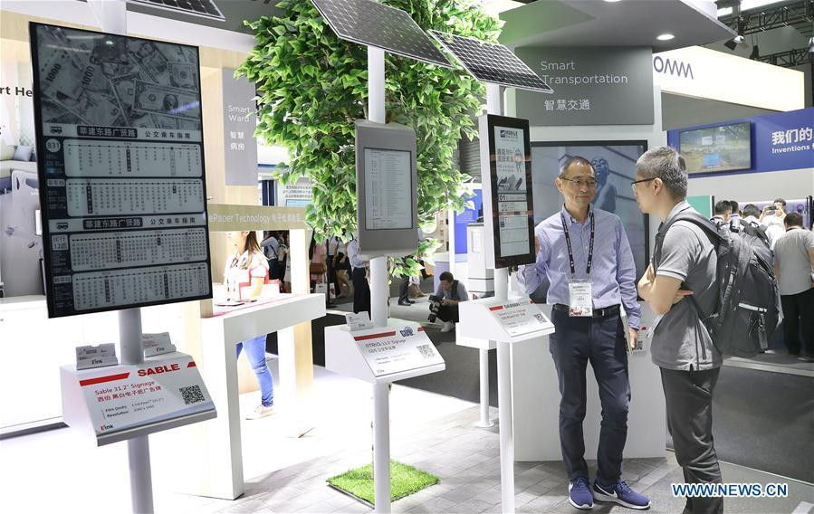 A staff member (L) introduces solar-powered bus stop display panels based on electronic ink and wireless network technologies during the Mobile World Conference Shanghai (MWCS) 2018 in east China\'s Shanghai, June 27, 2018. The three-day MWCS 2018 kicked off at the Shanghai New International Expo Center on Wednesday, showing trending mobile products, services and technologies. (Xinhua/Fang Zhe)