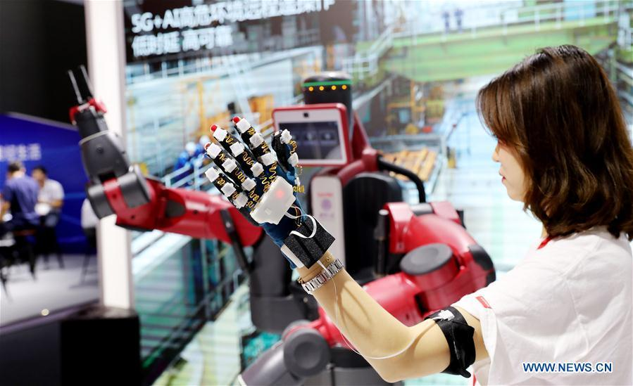 A staff member shows remote control with 5G and artificial intelligence (AI) technologies during the Mobile World Conference Shanghai (MWCS) 2018 in east China\'s Shanghai, June 27, 2018. The three-day MWCS 2018 kicked off at the Shanghai New International Expo Center on Wednesday, showing trending mobile products, services and technologies. (Xinhua/Fang Zhe)