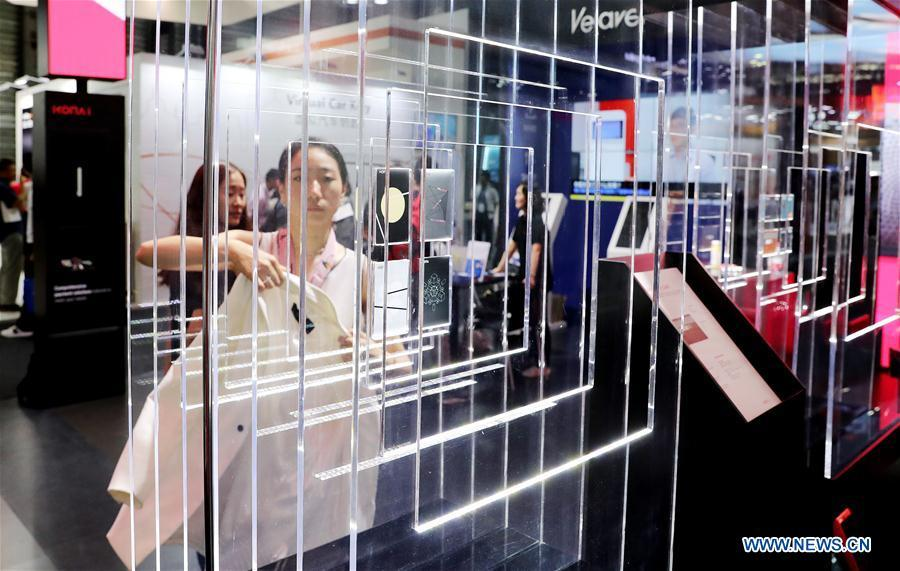 A visitor walks past an exhibitor booth during the Mobile World Conference Shanghai (MWCS) 2018 in east China\'s Shanghai, June 27, 2018. The three-day MWCS 2018 kicked off at the Shanghai New International Expo Center on Wednesday, showing trending mobile products, services and technologies. (Xinhua/Fang Zhe)