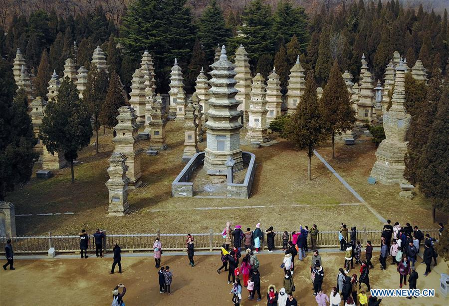 Tourists visit the Pagoda Forest of Shaolin Temple in Dengfeng City, central China\'s Henan Province, Jan. 30, 2017. The Pagoda Forest of Shaolin Temple has been the largest of its kind so far in China with over 230 pagodas. Pagodas built in ancient times in Henan act not only as landmarks for sight-seeing, but also as observers of the Chinese history. (Xinhua/Li An)