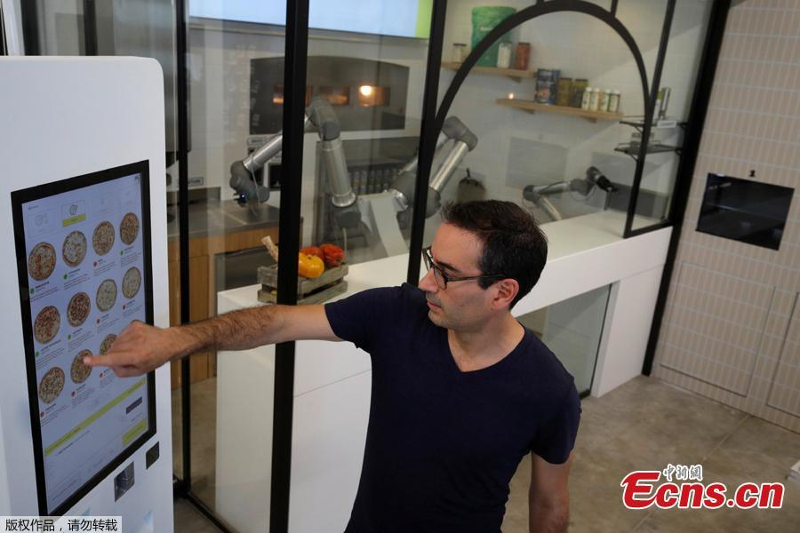 Philippe Goldman, CEO of French food startup EKIM, how to order pizza using a touch screen next to a pizzaiolo robot that prepares and cooks the pizza before the customer's eyes at their showroom in Montevrain near Paris, France, June 26, 2018. Picture taken June 26, 2018. (Photo/Agencies)