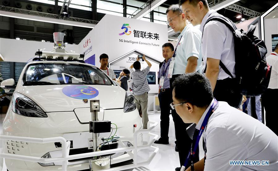 Visitors look at a wireless network device on a driverless car during the Mobile World Conference Shanghai (MWCS) 2018 in east China\'s Shanghai, June 27, 2018. The three-day MWCS 2018 kicked off at the Shanghai New International Expo Center on Wednesday, showing trending mobile products, services and technologies. (Xinhua/Fang Zhe)