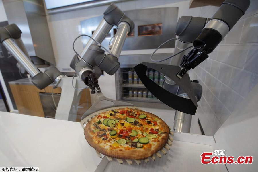 A pizzaiolo robot places a cooked pizza into its box before the customer's eyes at the showroom of French food startup EKIM in Montevrain near Paris, France, June 26, 2018. Picture taken June 26, 2018. (Photo/Agencies)