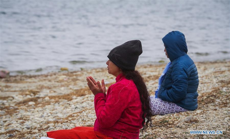 Indian pilgrims pray for blessing on the bank of Mapam Yumco Lake, a sacred Hindu and Buddhist site, in Ali Prefecture, southwest China\'s Tibet Autonomous Region, June 26, 2018. This year, the Nathu La Pass is expected to see about 500 officially-organized pilgrims from India who will make the 2,874-km pilgrimage, according to Yang Zhigang, deputy director of the office of foreign affairs and overseas Chinese affairs in Xigaze City. (Xinhua/Liu Dongjun)