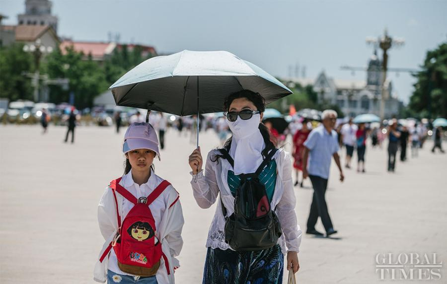 Tourists keep covered from the intense sunlight near Beijing\'s Tiananmen Square on Thursday. (Photo: Li Hao/GT)