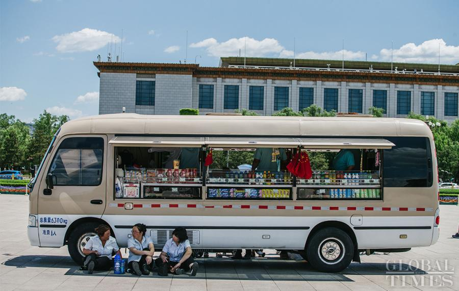 Workers at Tiananmen Square escape the heat in the shade of a mobile snack shop in Beijing on Thursday.  (Photo: Li Hao/GT)