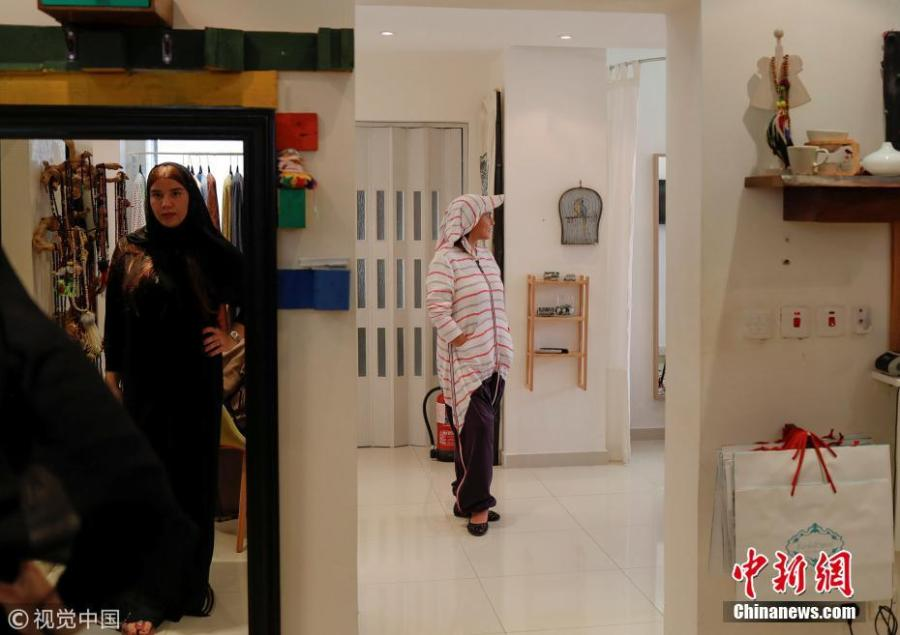 """Eman Joharjy(R), a fashion designer, and her employee (L) pose in creations at her shop in Jeddah, Saudi Arabia, June 23, 2018. In 2007, frustrated by a lack of abayas made for running or cycling, Joharjy designed one for herself. She began making them for friends and selling what she dubbed the """"sporty abaya"""". (Photo/Agencies)"""