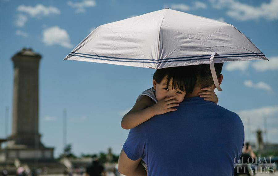 A father holds his son under an umbrella in Beijing on Thursday.  (Photo: Li Hao/GT)  Weather authorities in Beijing issued a yellow alert at 4:30 p.m. Thursday as a heat wave continues to scorch the region. As highs in the city are expected to hit above 35°C from June 29 to July 1, let\'s take a look at what locals and tourists are doing to escape the heat.