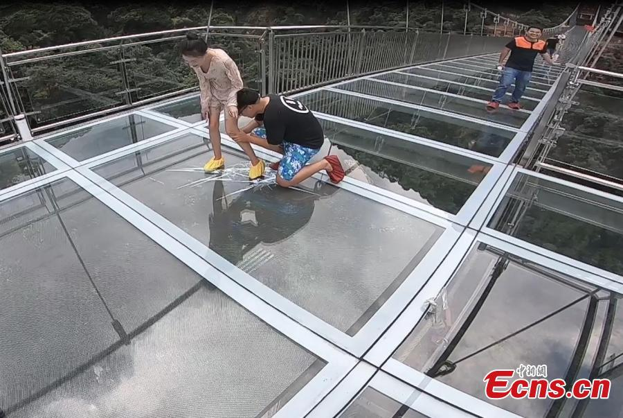 Tourist look at fake cracks on a vertigo-inducing glass bridge suspended over a valley in Qingyuan City, South China's Guangdong Province, June 28, 2018. The structure also features a massive circular glass observation deck suspended at the end of the bridge, jutting out 72 meters from the cliff edge. (Photo: China News Service/Xu Qingqing)
